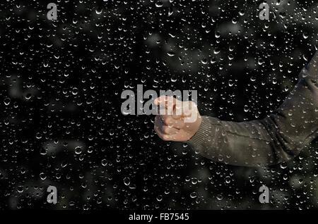 Main derrière une fenêtre humide Banque D'Images