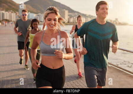 Portrait de jeune femme fit courir avec des amis sur la rue le long de la mer. Running club en formation de groupe à l'extérieur.
