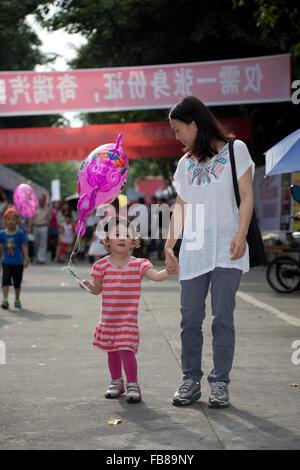 Un enfant de race mixte et sa mère chinoise lors d'un salon dans une ville en Chine. Banque D'Images