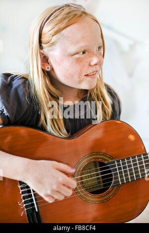 La Suède, Girl (8-9) en jouant de la guitare Banque D'Images