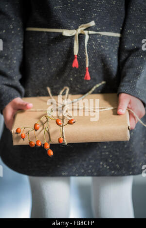 La Suède, Girl (6-7) holding wrapped Christmas present