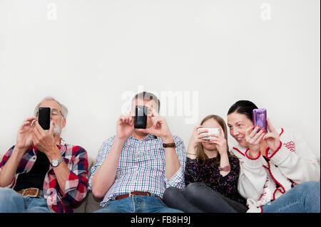 Girl (8-9) texting en famille sur canapé Banque D'Images