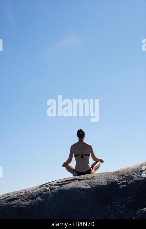 La Suède, l'Uppland, Runmaro Barrskar,, Rear view of woman practicing yoga on rock Banque D'Images