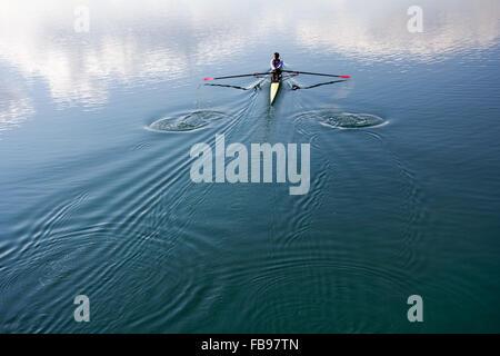 Jeune homme dans un bateau, de l'aviron sur le lac tranquille Banque D'Images