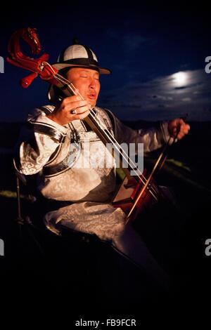 Un crin de cheval fiddler et guttural transmet les rythmes de chevaux et de la vie dans les steppes de Mongolie, Banque D'Images