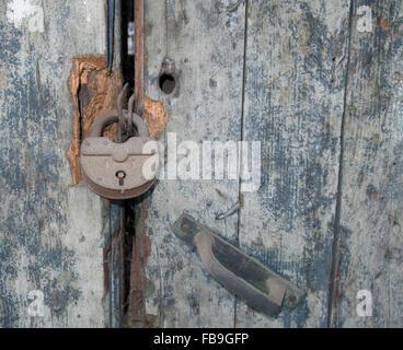 Old rusty metal cadenas sur la porte de bois minable Banque D'Images