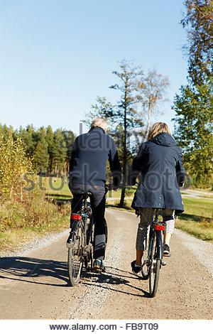 La Suède, Sodermanland, vue arrière de l'homme et de la femme à vélo Banque D'Images