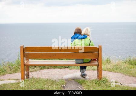 La Suède, Skane, Kullaberg, Kullen, Mère et fils (8-9) sitting on beach et à la recherche en mer Banque D'Images
