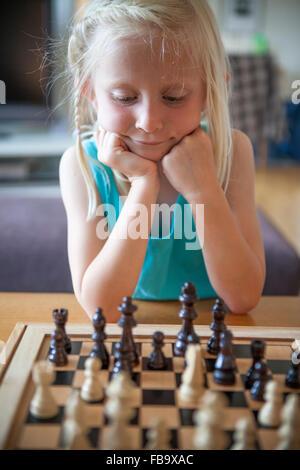 La Suède, Vastergotland, Lerum, Girl (8-9) en jouant aux échecs dans la salle de séjour Banque D'Images