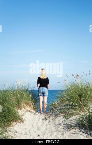 La Suède, Skane, Soderslatt Beddinge,, vue arrière du blond woman standing on beach et à la recherche en mer Banque D'Images