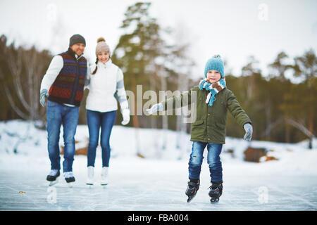 Happy kid sur patins en patinoire avec ses parents derrière Banque D'Images