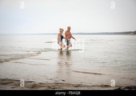 La Suède, Stockholm, l'Ahus, Senior couple pataugeant dans l'eau Banque D'Images