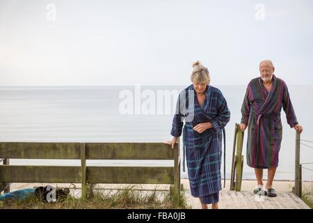 La Suède, Stockholm, l'Ahus, Senior couple revenant de la plage, dans des peignoirs Banque D'Images