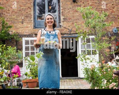 La Suède, Skane, Vemmerlov Osterlen, Ostra, Portrait of woman holding tray with food Banque D'Images