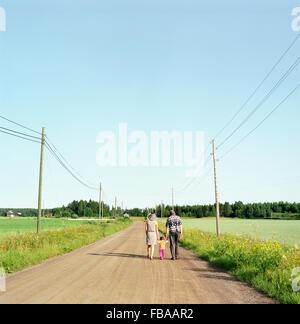 La Finlande, Uusimaa, Lapinjarvi, vue arrière de personnes avec enfant (2-3) marcher le long chemin de terre Banque D'Images