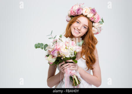 Smiling attractive young woman avec longs cheveux rouges en gerbe holding bouquet de fleurs sur fond blanc
