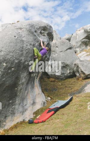 La NOUVELLE ZELANDE, Castle Hill, jeune homme grimpant boulder avec deux tampons crash préparé sous Banque D'Images