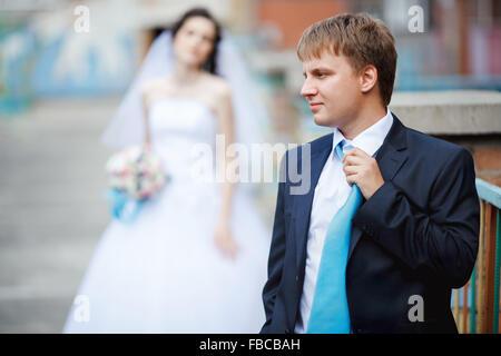 Le marié costume bleu foncé turquoise redresse cravate avec un visage aigre en arrière-plan, fatigué et frustré Banque D'Images