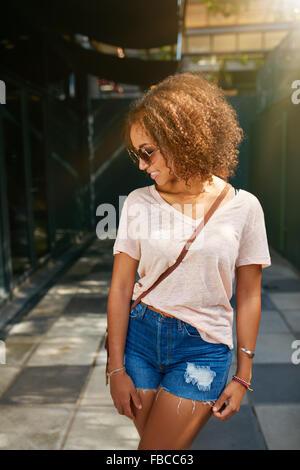 Young African American city girl. Elle porte tenue décontractée, lunettes de soleil et à la recherche vers le bas.