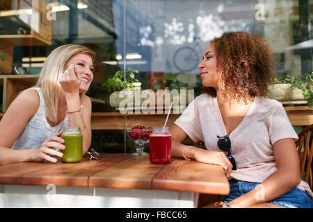 Deux femmes heureux assis dans un restaurant en plein air. Female friends enjoying drinks et chat at sidewalk cafe.