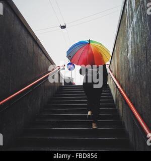 Rear View of Woman Holding Umbrella et marche sur Escalier Banque D'Images