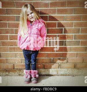 Portrait de petite fille faisant un visage tout en se tenant contre le mur