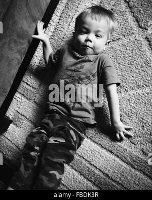 Garçon couché sur un tapis Banque D'Images