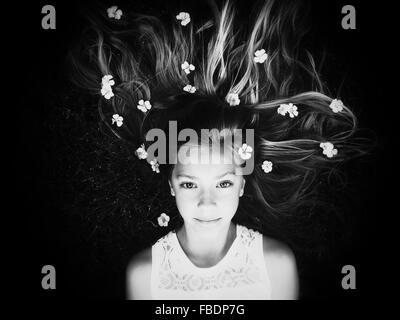 Portrait de jeune fille couchée avec des fleurs dans les cheveux Banque D'Images