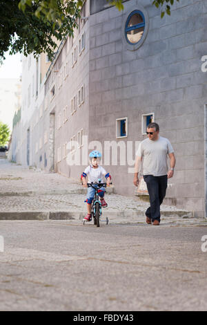 Man Looking At Boy Riding Bicycle In City Banque D'Images