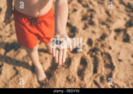 Up de garçon montrant galets sur la plage Banque D'Images