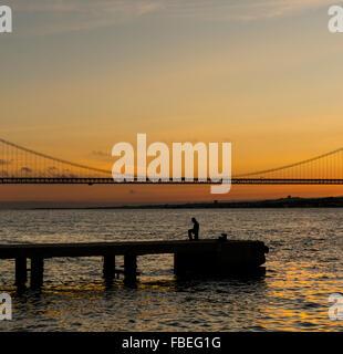 L'homme silhouette sur la jetée sur le fleuve Tage contre le ciel au coucher du soleil Banque D'Images