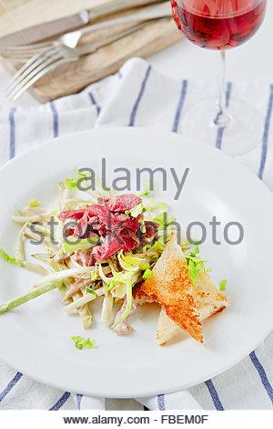 Céleri salade verte rôti de bœuf servi avec du vin rouge Banque D'Images