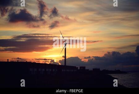 Silhouette Éolienne au Beach contre ciel nuageux pendant le coucher du soleil Banque D'Images