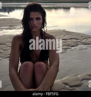 Portrait de belle jeune femme assise sur le rivage à Beach Banque D'Images