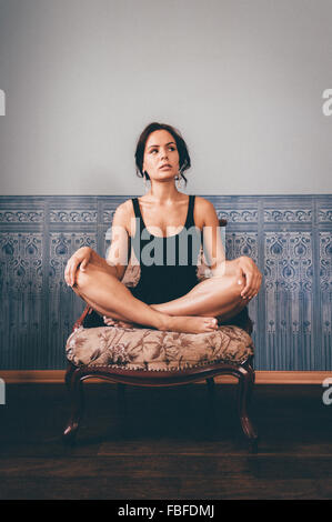 Jeune femme avec les jambes croisés assis sur un fauteuil contre le mur à la maison Banque D'Images