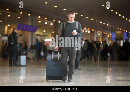 Young smiling handsome man in 20s walking in airport terminal moderne, à l'aide de smart phone app dans les zone Banque D'Images