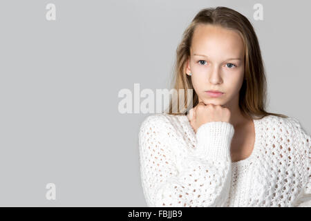 Portrait de belle accent pensive casual caucasian woman wearing white chandail tricoté, studio image, fond gris Banque D'Images