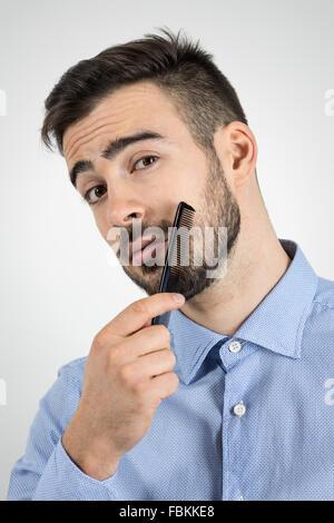 Portrait de jeune homme barbu se peigner sa barbe en regardant la caméra. Portrait studio gris désaturé sur l'arrière Banque D'Images
