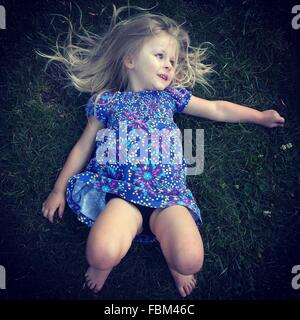 High Angle View of a Girl Lying On Grass Banque D'Images