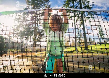 Girl standing on tennis filet de levage Banque D'Images