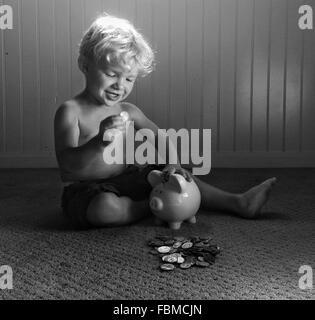 Garçon jouant avec de l'argent et piggy bank Banque D'Images