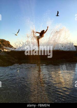 Woman in yoga pose arc encore sur les falaises at beach Banque D'Images
