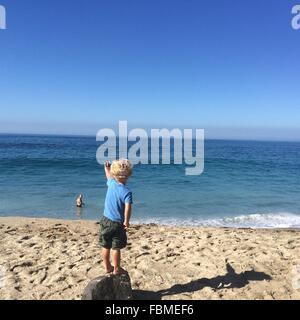 Vue arrière du garçon debout sur la plage de roche à la forme au père Banque D'Images