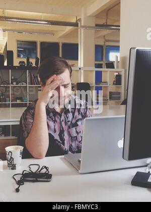 Homme assis en face de l'ordinateur portable Banque D'Images