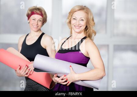 Portrait intérieur d'un groupe de deux femmes âgées gaies fit attrayant posing holding Tapis de fitness, l'élaboration Banque D'Images