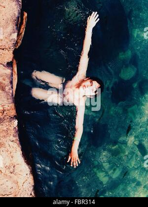 High Angle View Of Shirtless Boy swimming in Sea Banque D'Images