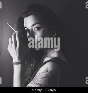 Portrait d'une jeune femme qui fume sur fond uni Banque D'Images