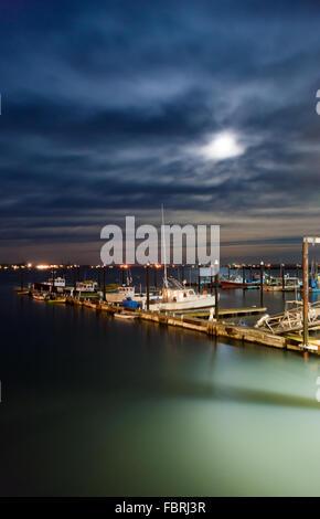 Lever de lune dans le port de Provincetown, Cape Cod, Massachusetts, avec les bateaux de pêche amarrés au quai sous Banque D'Images