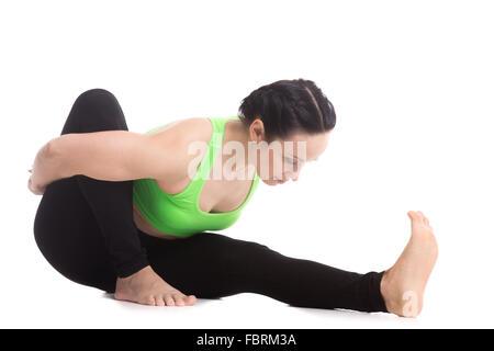 Athletic belle fille pratique le yoga, s'asseoir, se pencher en avant en Marichyasana je pose, dédiée à la Sauge Banque D'Images