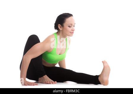Smiling sporty belle fille pratique le yoga, s'asseoir, se pencher en avant en Marichyasana je pose, dédiée à la Banque D'Images